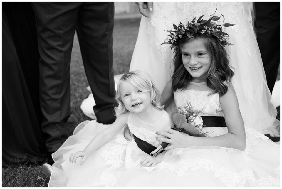 A picture in black and white of two flower girls smiling as they sit on the grass in their beautiful dresses at a Station 67 Columbus OH wedding by Alayna Parker Photography