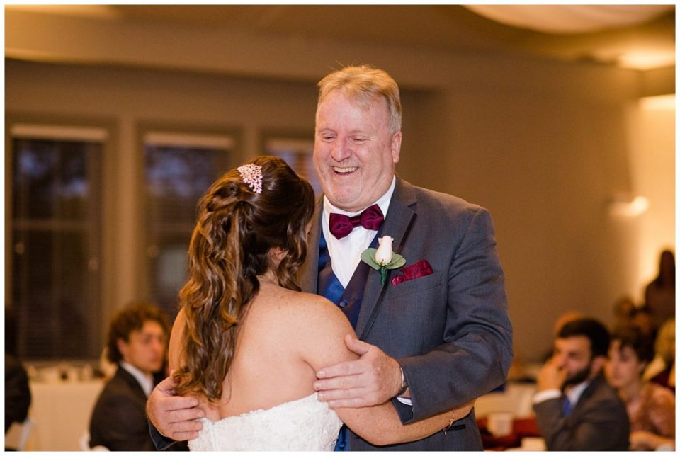 father smiling at bride while he dances with her