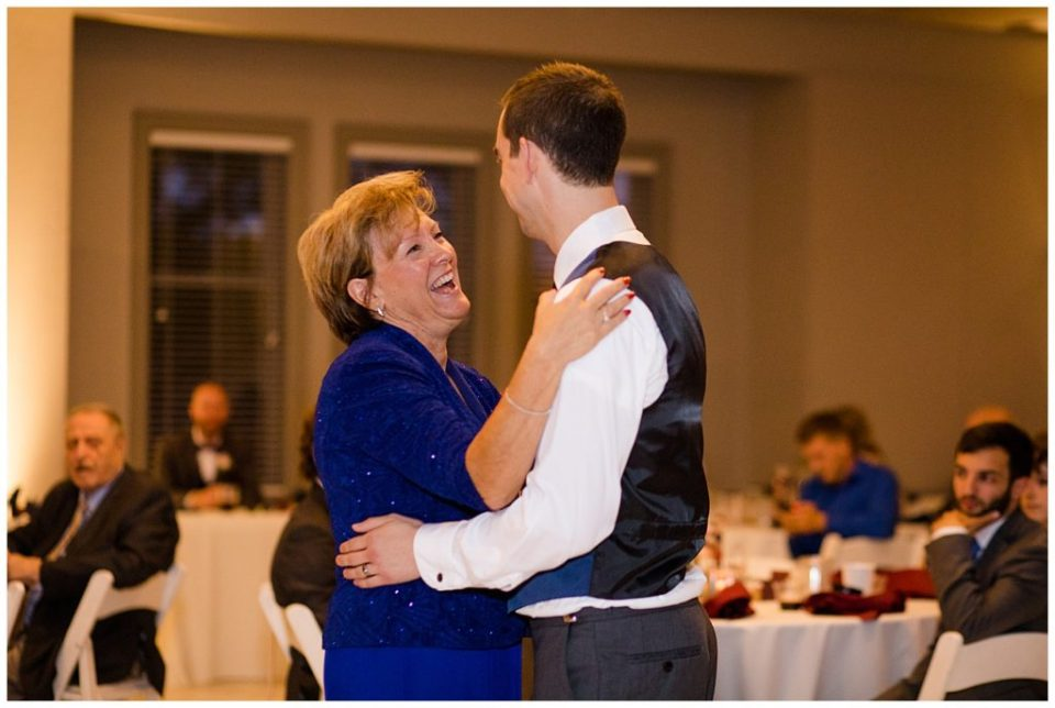 mother laughing while she dances with groom