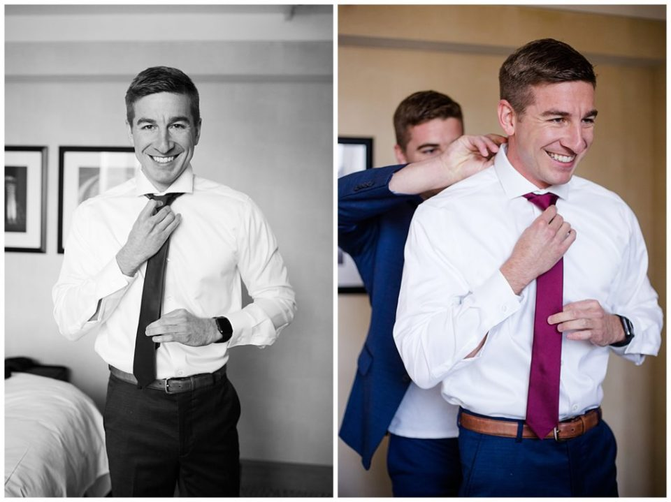 A photograph of a smiling groom adjusting his tie with help from his best man as he gets dressed for his wedding by Columbus OH wedding photographer, Alayna Parker Photography