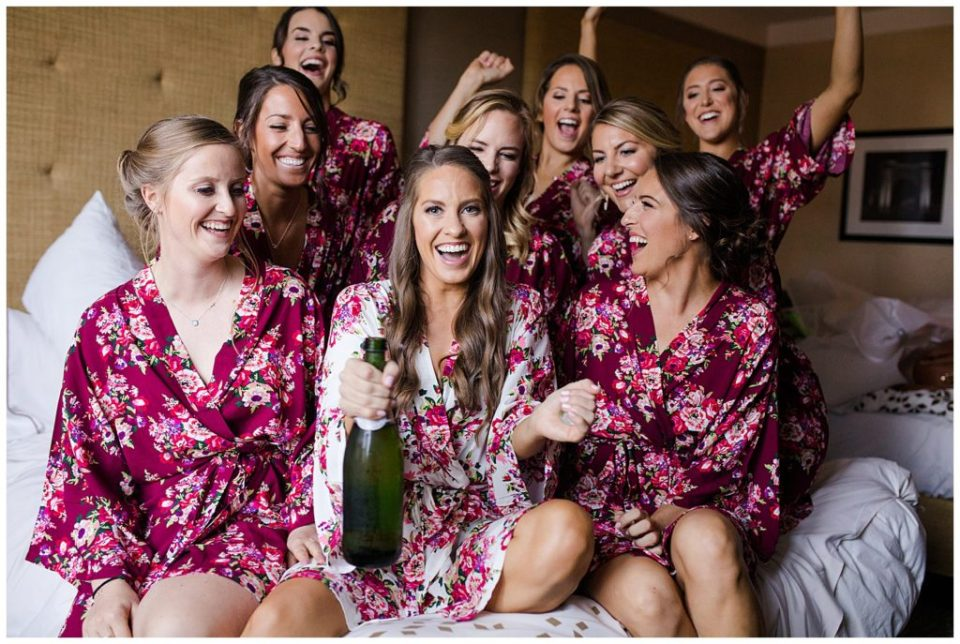 An image of a bride laughing and relaxing with her bridesmaids before they get ready for the wedding ceremony by Columbus Ohio wedding photographer, Alayna Parker Photography