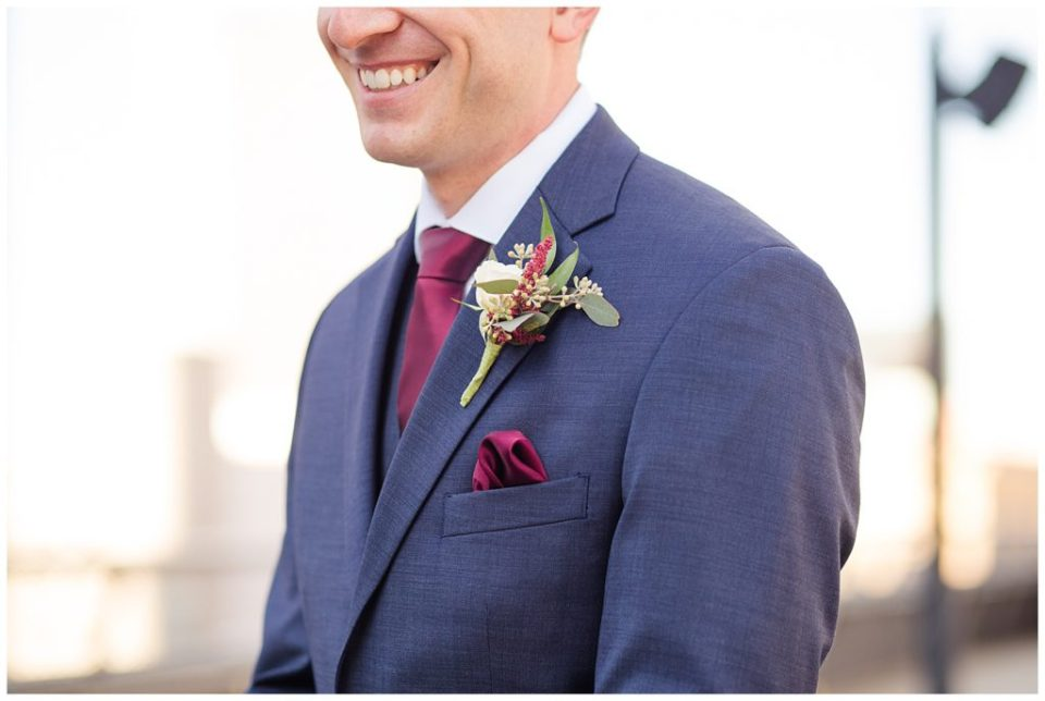close up of groom's boutonniere with white rose and eucalyptus