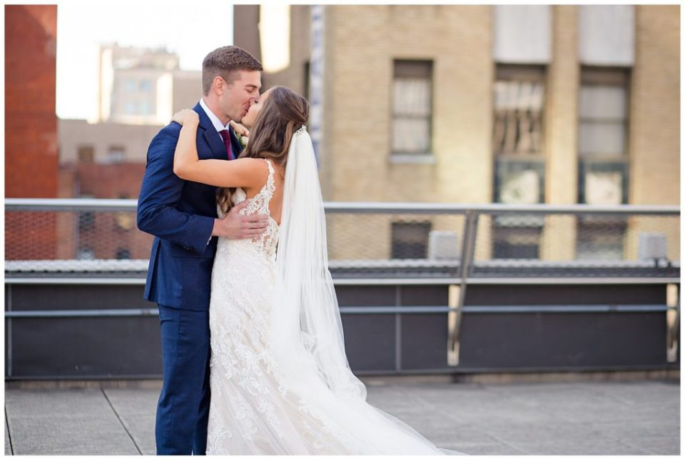 close up of bride and groom kissing after first look on rooftop at renaissance hotel