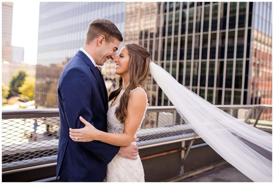 bride and groom laughing as veil blows in wind on rooftop at renaissance hotel