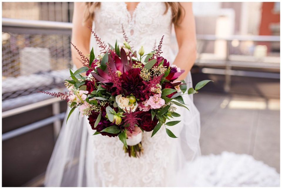 close up of bride holding bouquet of burgundy, pink, and white flowers and greenery