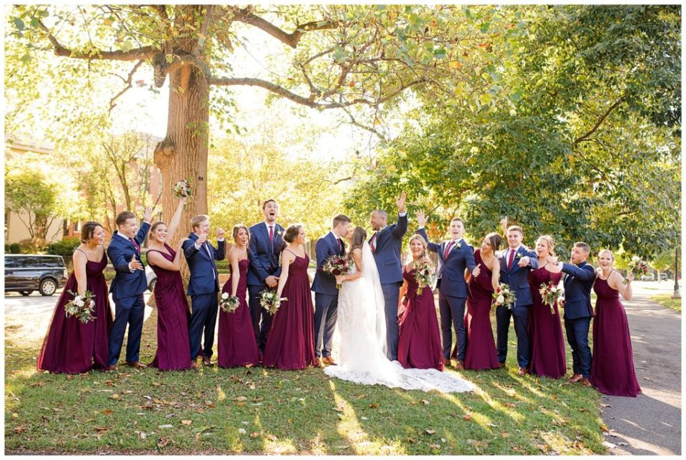 bride and groom kissing while bridal party cheers at schiller park in german village