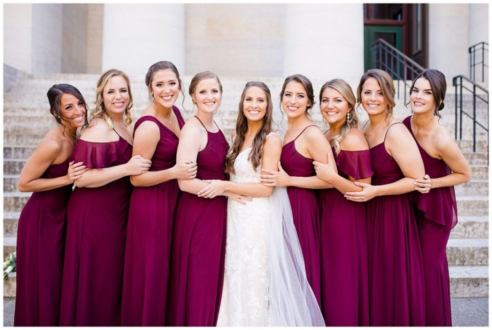 bride and bridesmaids holding on to each other and smiling at camera outside ohio statehouse