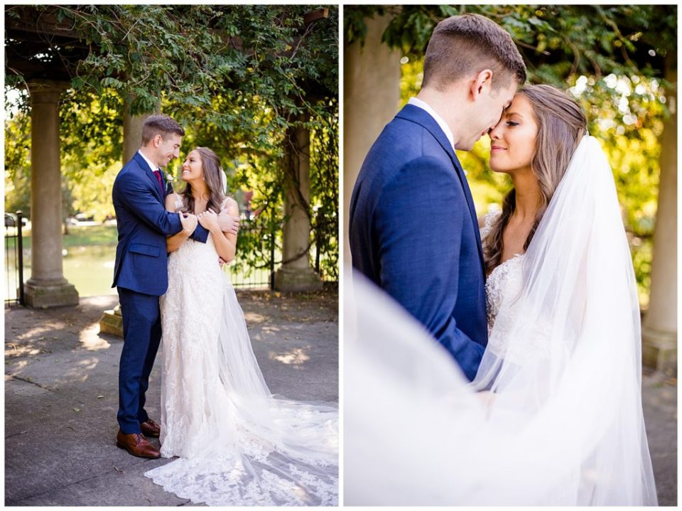 bride and groom touching foreheads while veil blows in wind at schiller park in german village
