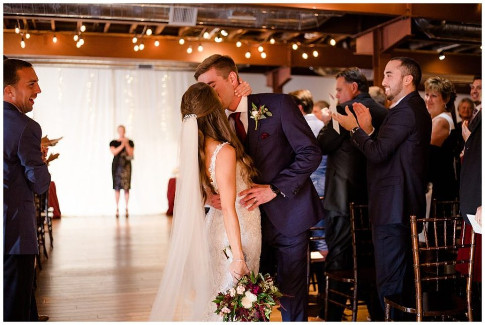 bride and groom share kiss at end of aisle at copius