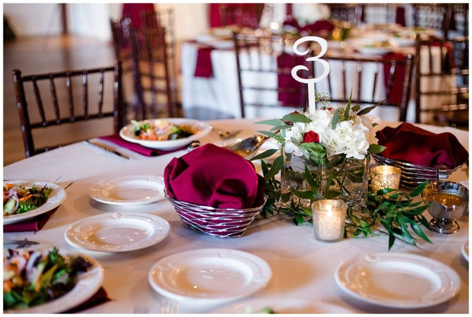 white and greenery centerpiece at copius