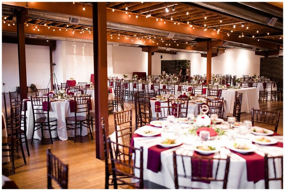 round tables with wooden chairs, white tablecloths, and burgundy cloth napkins at copius