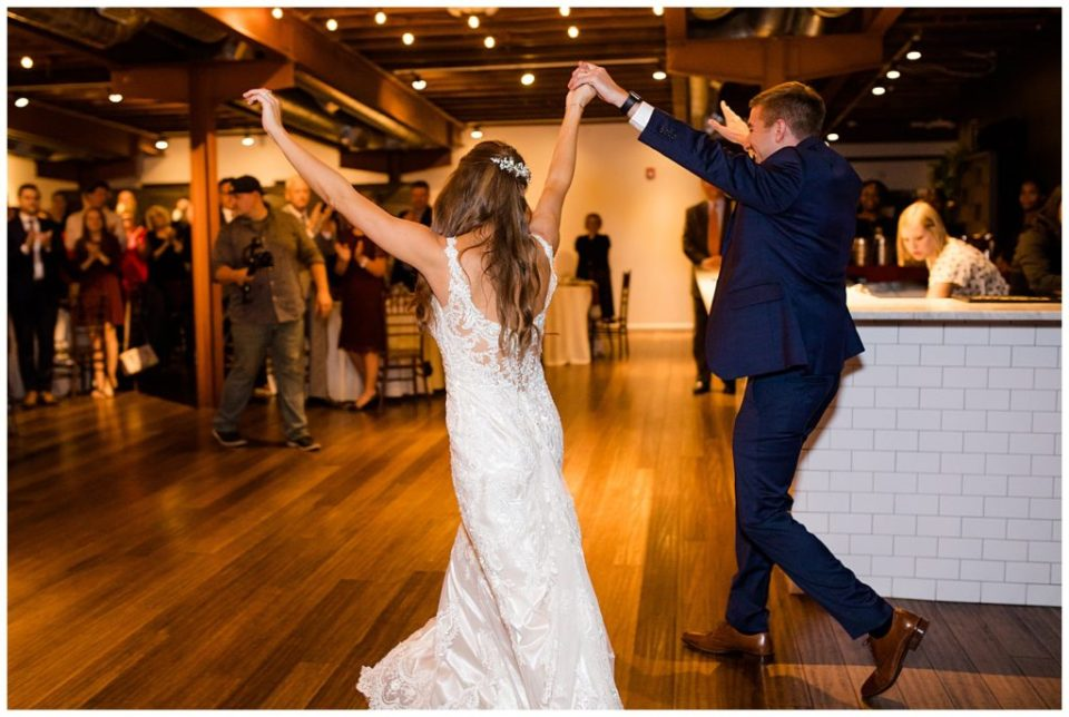 bride and groom throwing hands in air as they enter reception at copius