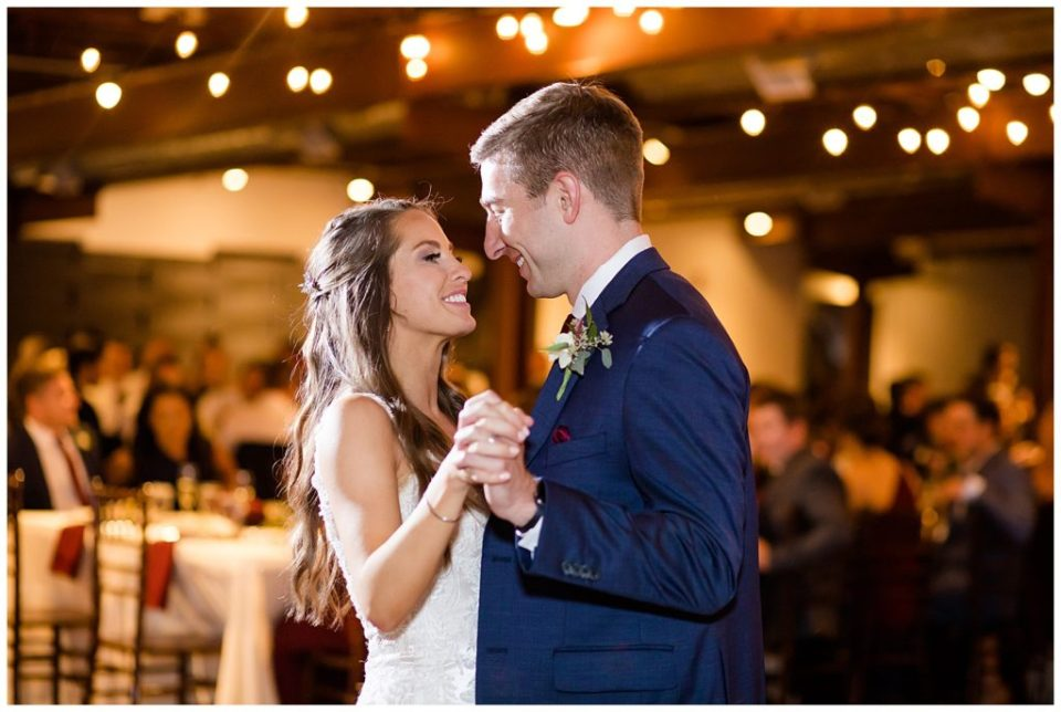 bride and groom smiling at each other while they share first dance at copius