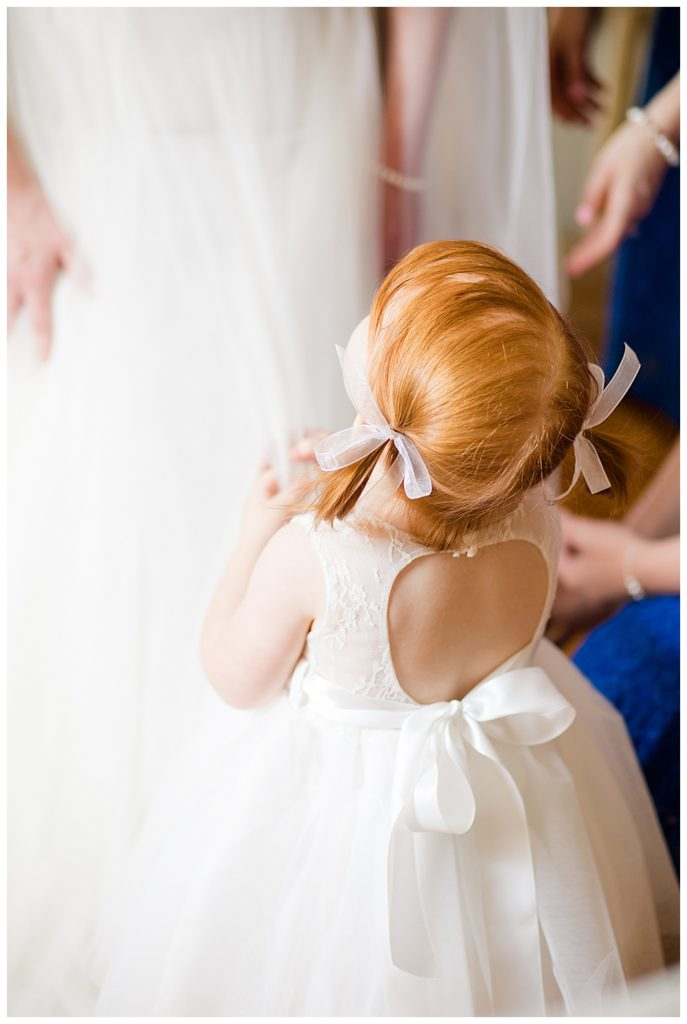 little red headed girl in pigtails looking up at bride