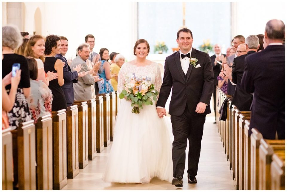 A picture of the bride and groom walking down the aisle after the wedding ceremony, smiling and holding hands at a Nationwide Hotel and Conference Center wedding by Columbus  wedding photographer, Alayna Parker Photography
