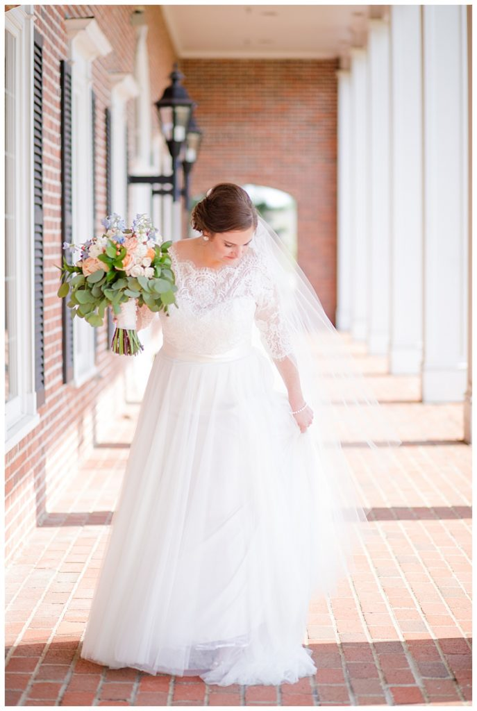 An image of the bride in her gorgeous dress and veil, gazing down, holding her bouquet, glowing in sunlight on a portico at a Nationwide Hotel and Conference Center wedding by Columbus Ohio wedding photographer, Alayna Parker Photography