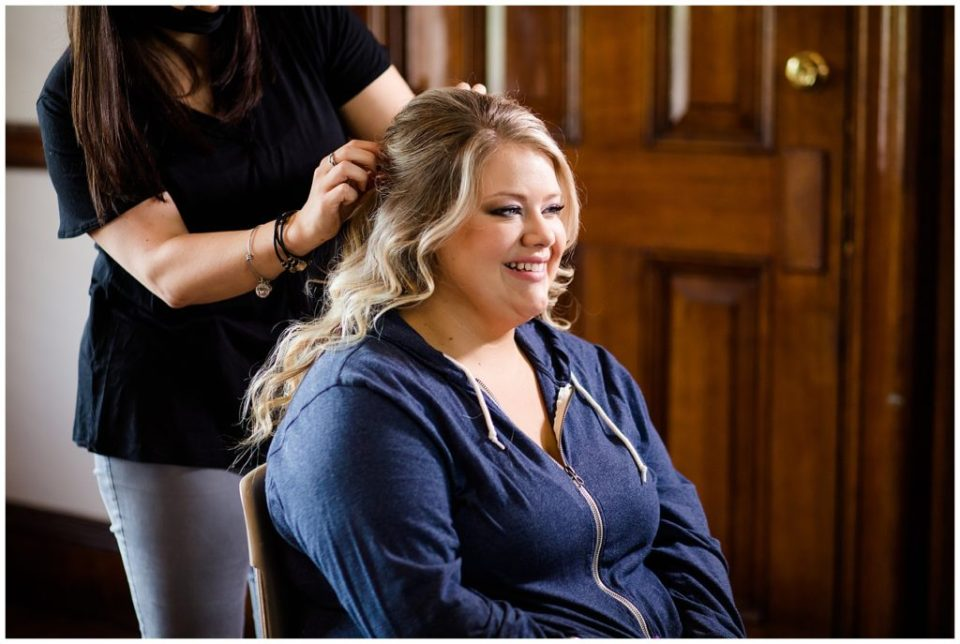 bride smiling while hair is being styled at the postmark