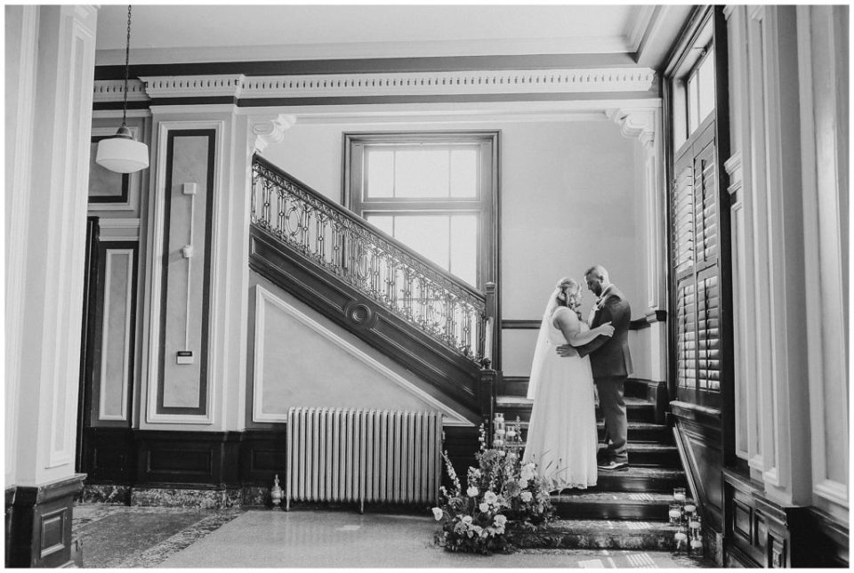 black and white image of bride and groom on staircase at the postmark