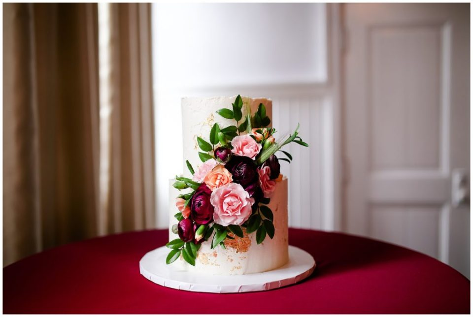 white wedding cake with pink and burgundy flowers at the postmark
