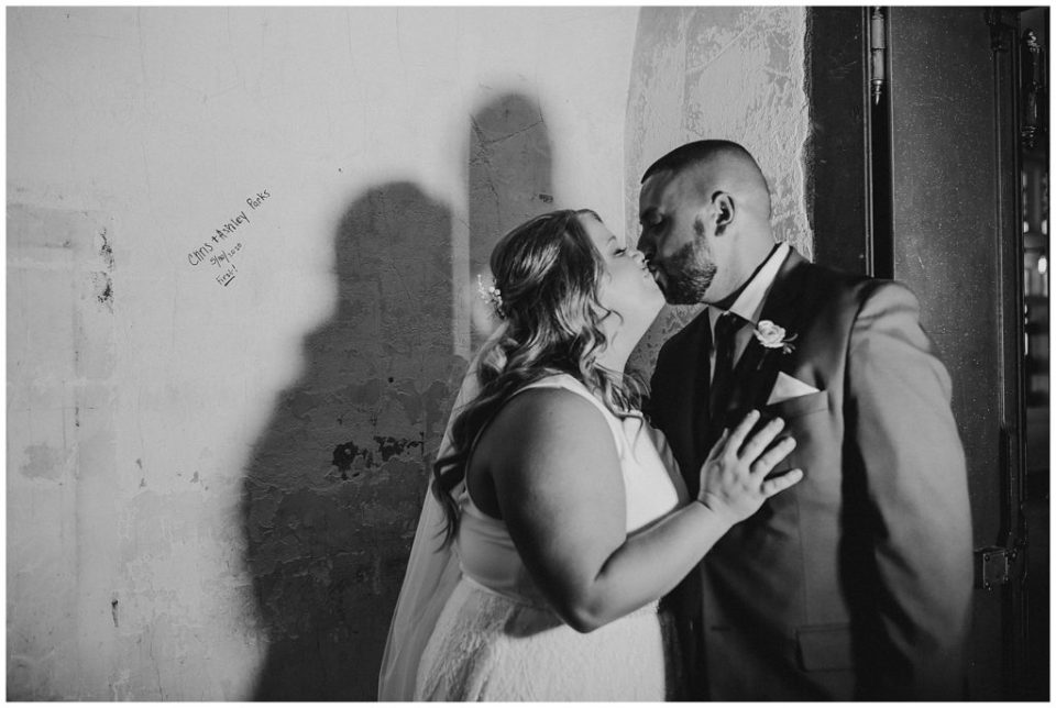black and white image of bride and groom siging the vault at the postmark