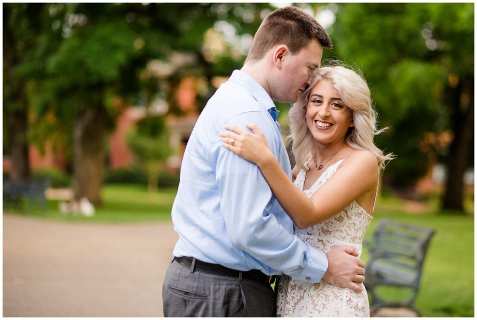 A picture of a newly engaged couple embracing as the man gently touches his fiancee's forehead while she smiles and touches his shoulder, showing her new engagement ring at Schiller Park near German Village in Columbus Ohio