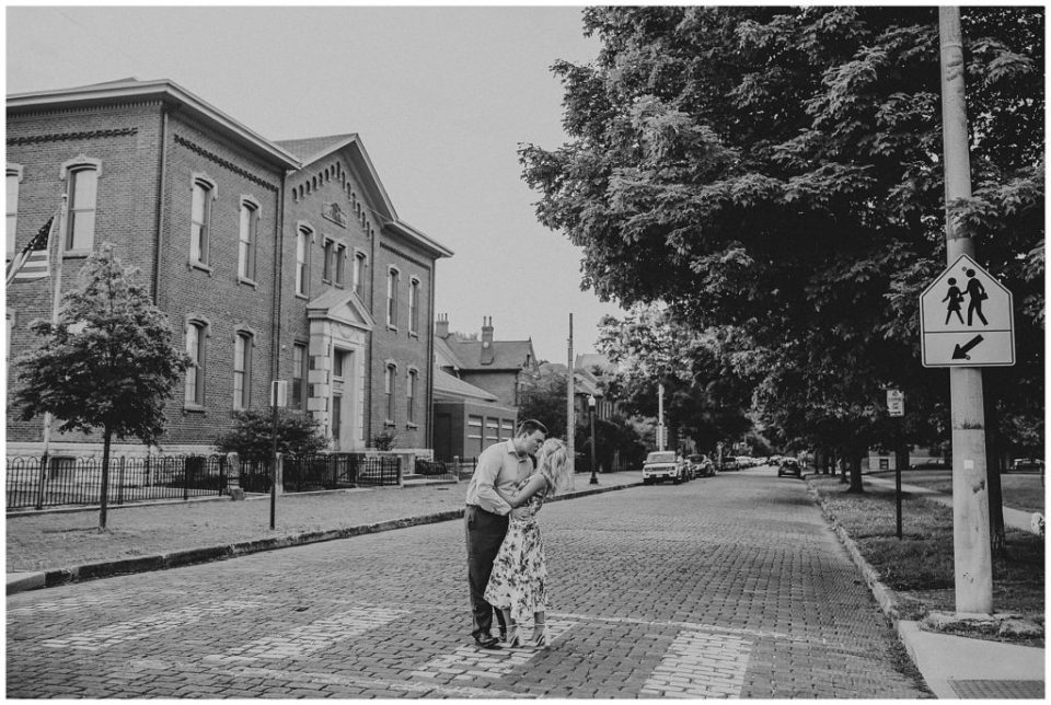 A picture in black and white of a newly engaged couple at a distance romantically kissing as they stand in a brick road with a vintage building in the background by Alayna Parker Photography an engagement photography in Columbus