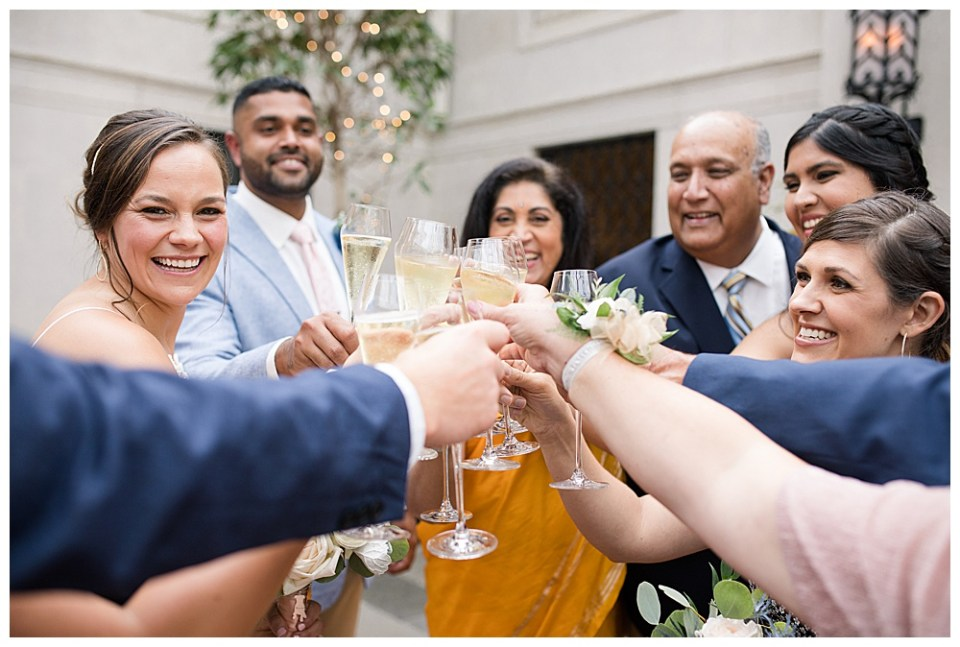 An image of a bridal couple toasting champagne glasses with the family members after the wedding ceremony in the Columbus Museum of Art on E Broad St, Columbus Ohio