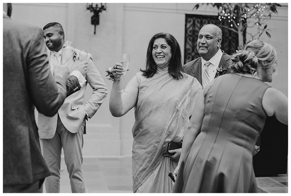A photograph in black and white of the groom's mother raising her champagne glass as the wedding guests share in the happiness of the marriage after the ceremony in a Columbus Museum of Art wedding