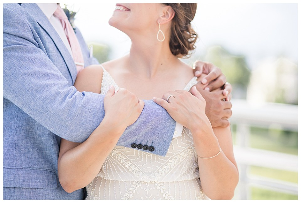 A photograph of a closeup view of a groom wrapping his arms around his bride as she holds his arm, showing her new wedding ring in the Columbus Museum of Art