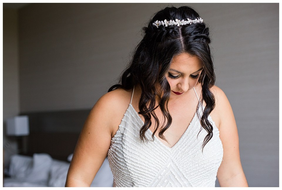 A photograph of the bride with her hair and makeup done, dressed for the wedding in her head piece and beaded wedding dress, pausing to look down for a moment at Dorral Farm in Marysville, OH