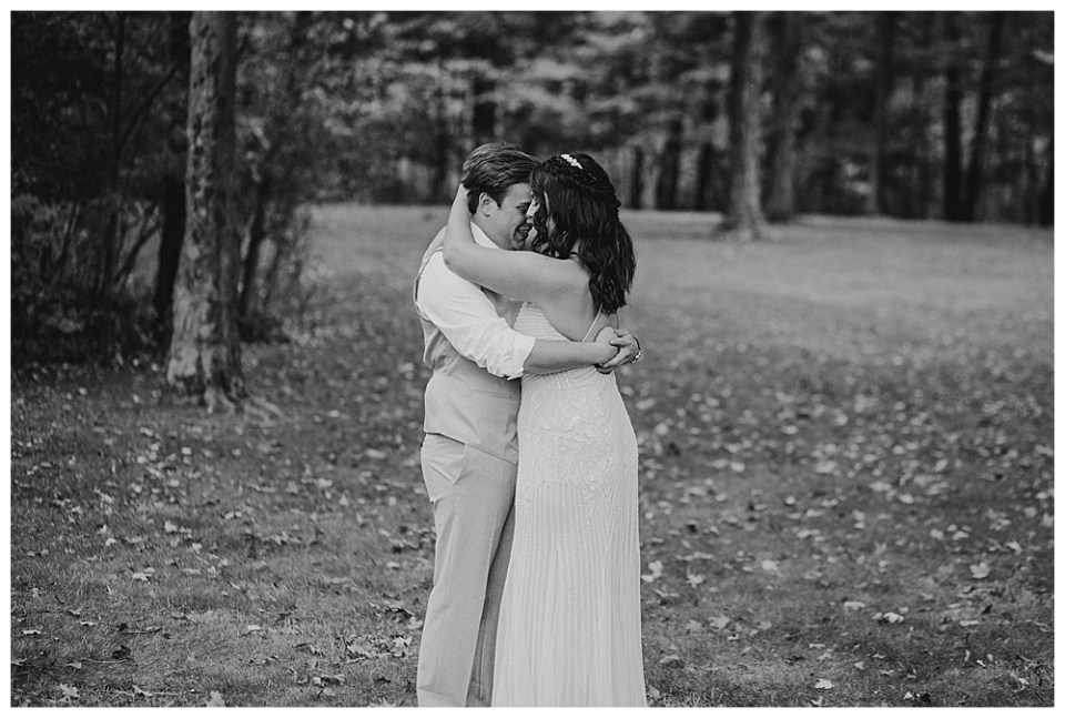 A picture of the bride and groom holding hands outdoors as we see them happy during their first look outdoors in a park-like setting