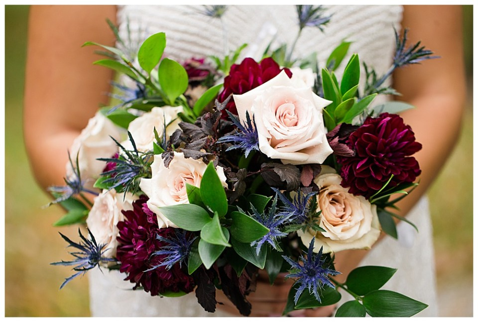 A picture of a closeup view of the bride's beautiful bouquet of red, light pink, and blue flowers with delicate greenery, with the bride's white dress showing behind it at Dorral Farm in Marysville, OH