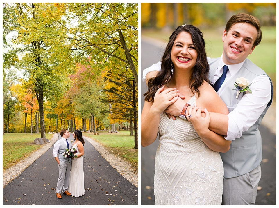 A picture of the bride and groom standing close together on a quiet park road gazing at each other with a backdrop of fall trees and a view of the groom hugging the bride from behind as they both laugh