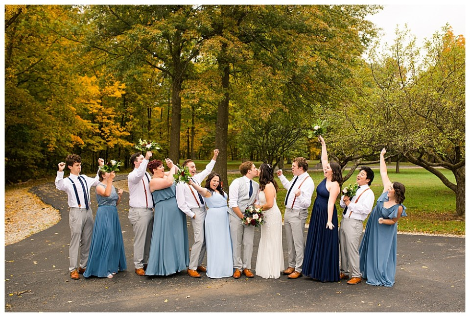 A photograph of the bride and groom standing with their wedding party while the group cheers on the bridal couple as they kiss at Dorral Farm in Marysville, OH