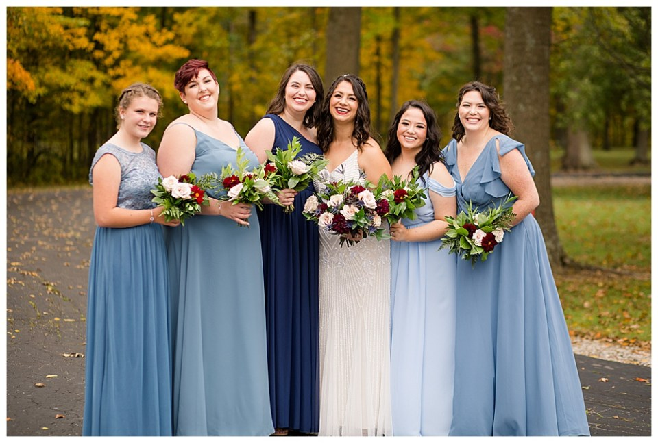 A picture of the bride and her bridesmaids standing together, smiling in their stunning long blue dresses, holding their bouquets at Dorral Farm in Marysville, OH