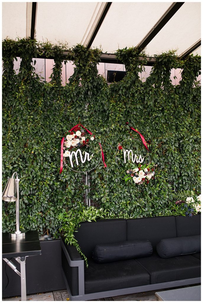 "A picture of a wall totally covered with green vines and ""Mr"" and ""Mrs"" signs, a backdrop at a seating area at the outdoor wedding reception venue"