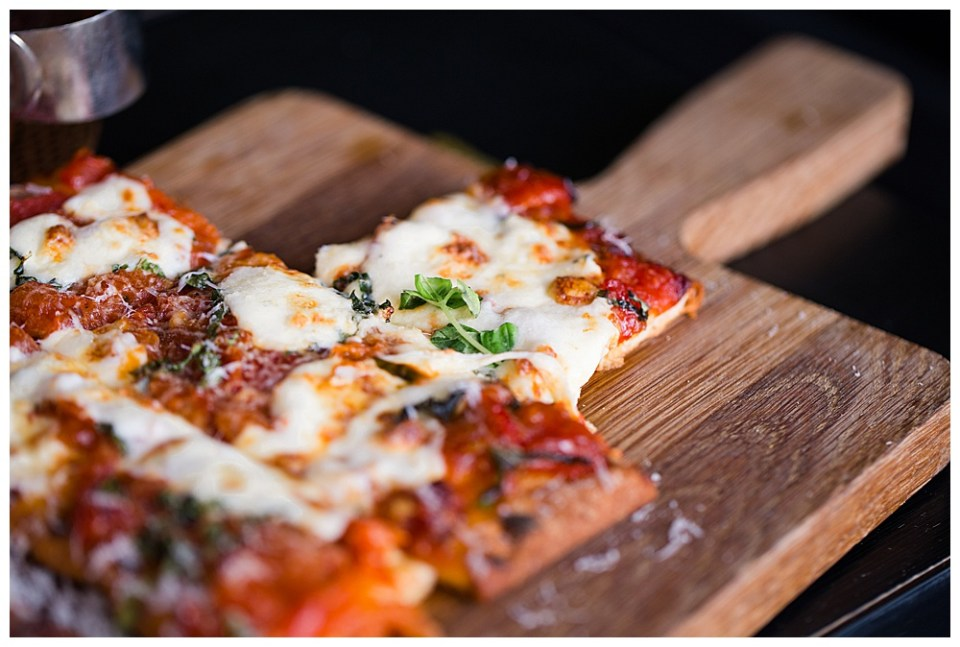 A picture up close of a gourmet pizza cut and waiting on a wooden serving board for wedding guests at the reception