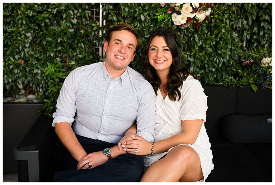 An image of the bride and groom sitting arm in arm, now in casual clothes, smiling and relaxing at their outdoor wedding reception as a lovely wall of greenery fills the background