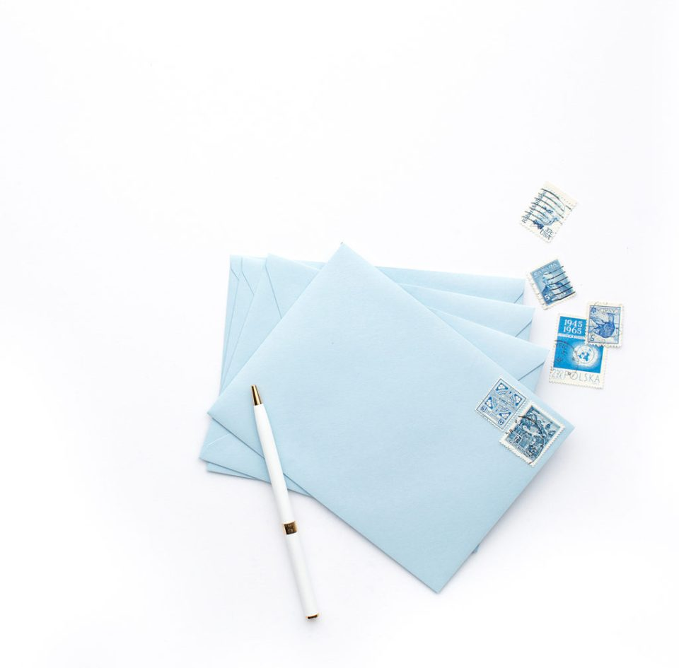image of light blue envelopes, stamps, and a white pen as a header for the question should you send save the dates
