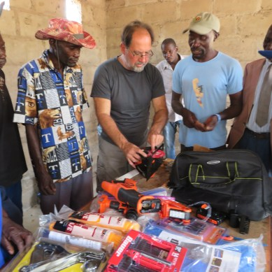 A team member shows men how to use battery operated power tools in Chikandakubi. They will use these tools to build coffins. Income will help families purchase food and other essentials.