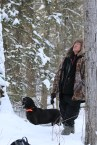 Houndsman Lorne and his dog watch a treed cougar