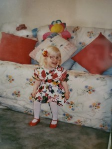 A young toddler smiles happily in a dress with red and blue flowers on it. She has a red flower in her blonde hair and glasses.