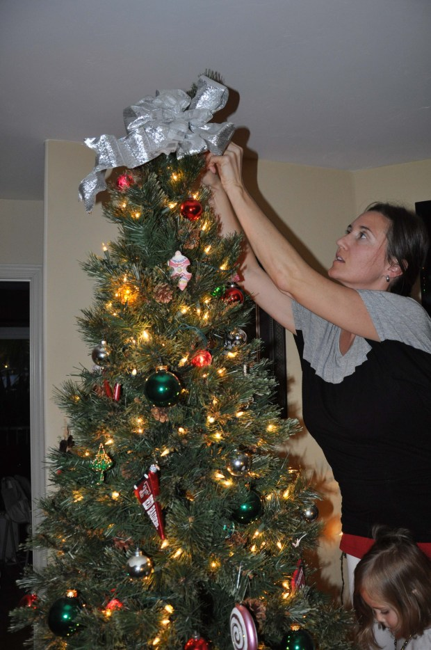 Momma topping the tree. We need a star, one of these years we will get around to it.