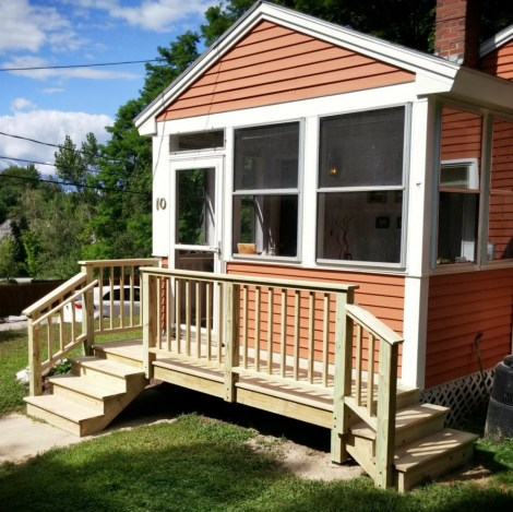 A small porch with a handrail mounted with weather-proof stainless hardware.