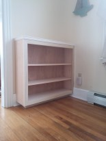A small, unfinished built-in bookshelf.