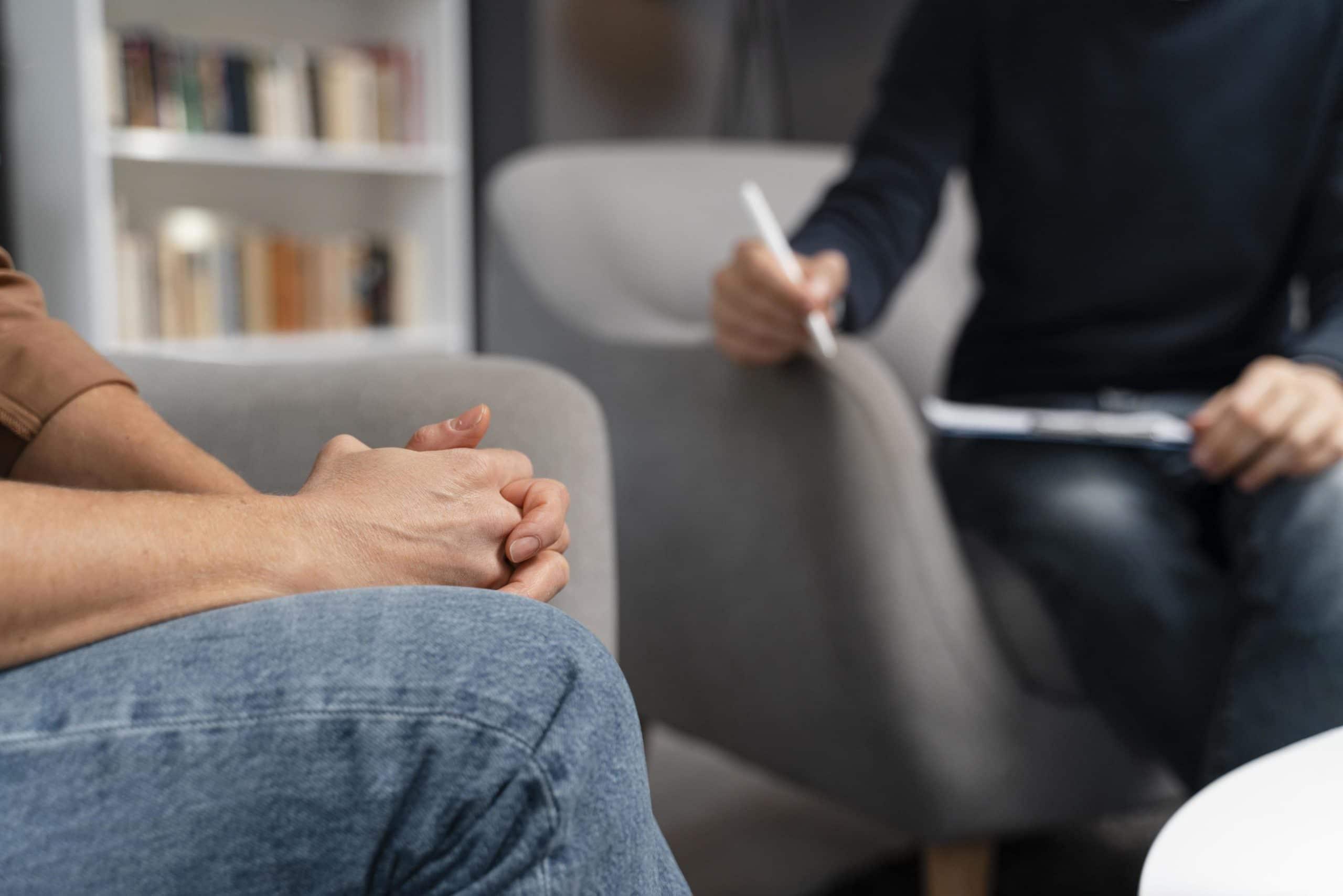 focus sur les mains d'une personne avec en flou quelqu'un qui prend des notes