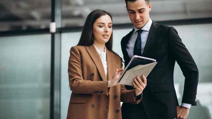 une femme avec un carnet qui discute avec un homme en costume