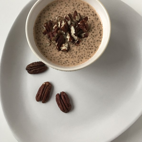 A bowl of Chia and pecan porridge with three pecan nuts on one side