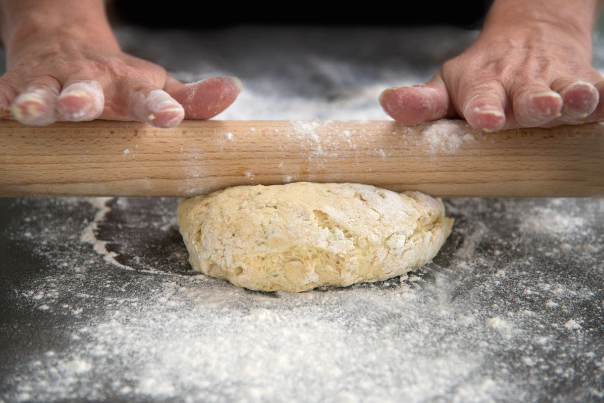 Two hands on a rolling pin - rolling pastry