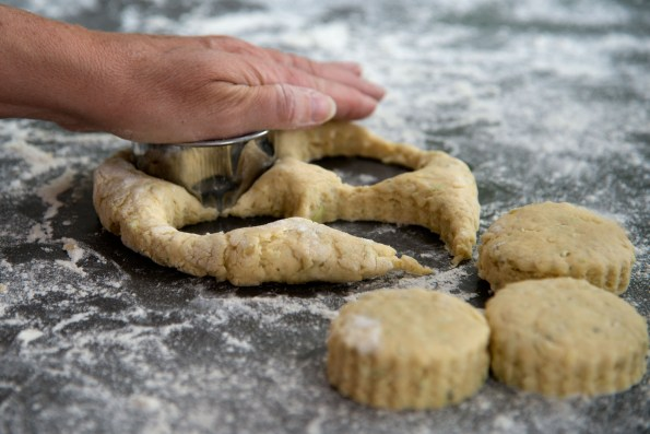 A hand on a pastry cutter, cutting three scones